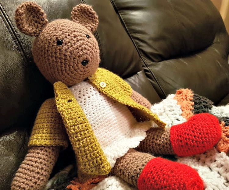 a bear made of crochet in brown wool with a  white dress, green cardigan and red boots, sitting on the sofa