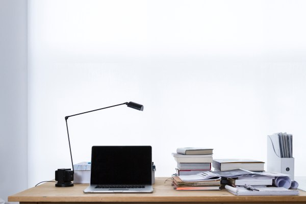 a laptop on a desk with a lamp and lots of books