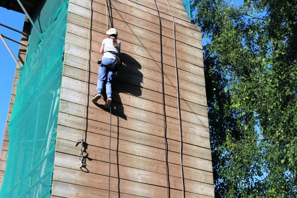 a young girl abseiling down a wall