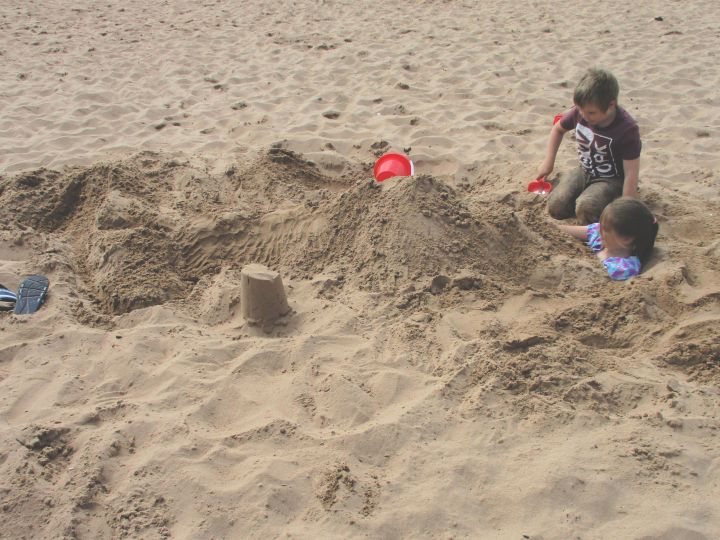 a little girl buried in the sand on the beach while her brother digs more sand