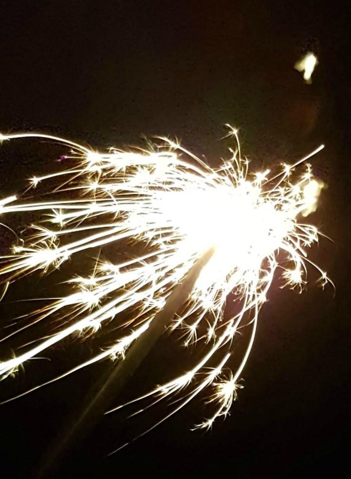 a bright sparkler against a dark background