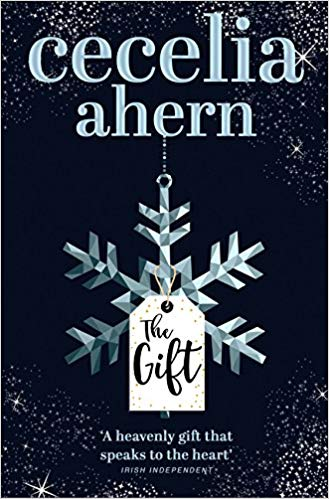 book cover, black background with a  gift tag attached to a snowdrop.