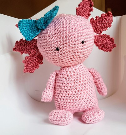 pink crochet axolotl with a blue bow