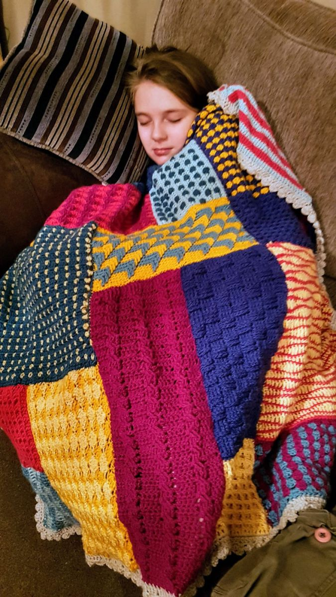 Little girl sleeping on sofa covered with a patchwork crochet blanket