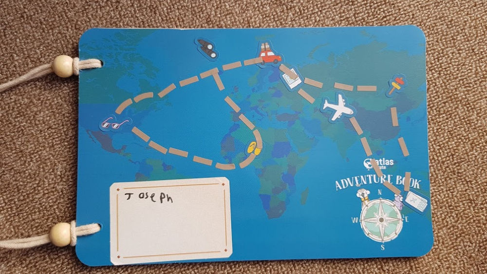 cover of the Adventure book, showing a blue page with a map of the world decorated with stickers