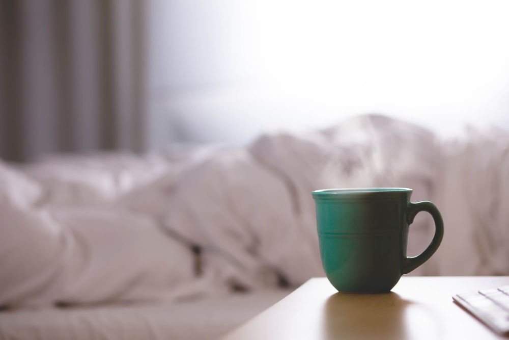 photograph of a mug in foreground with a bed in the background