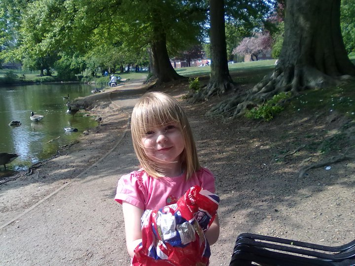 a little girl standing by a duck pond