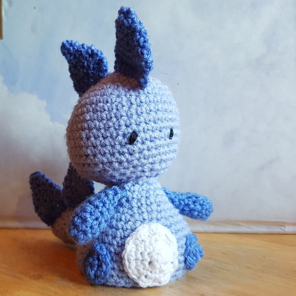 a crochet egg cosy dragon in two shades of blue
