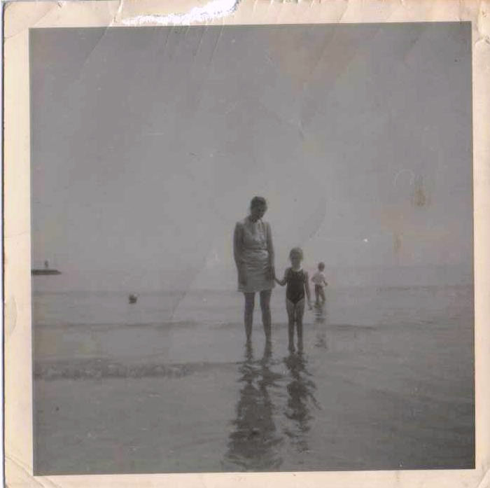 black and white photo of a woman and a little girl paddling in the sea.