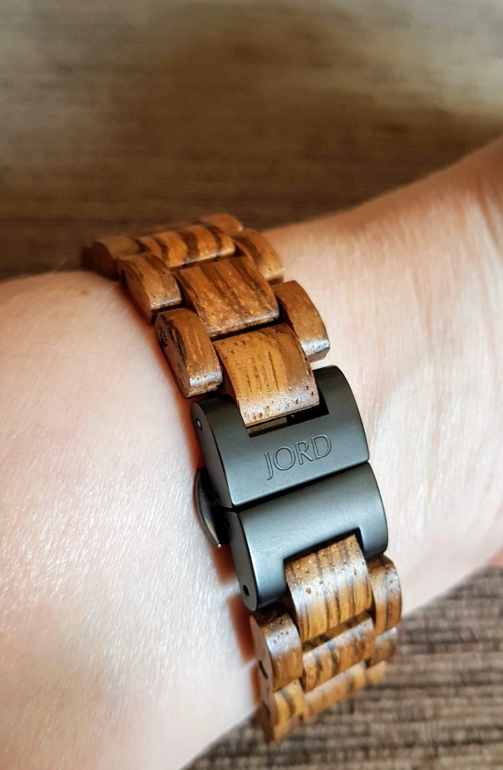 A close up photo of the watch clasp which is black against the zebra wood.