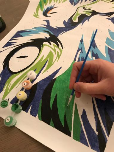 image of a hand painting a paint by numbers cat picture