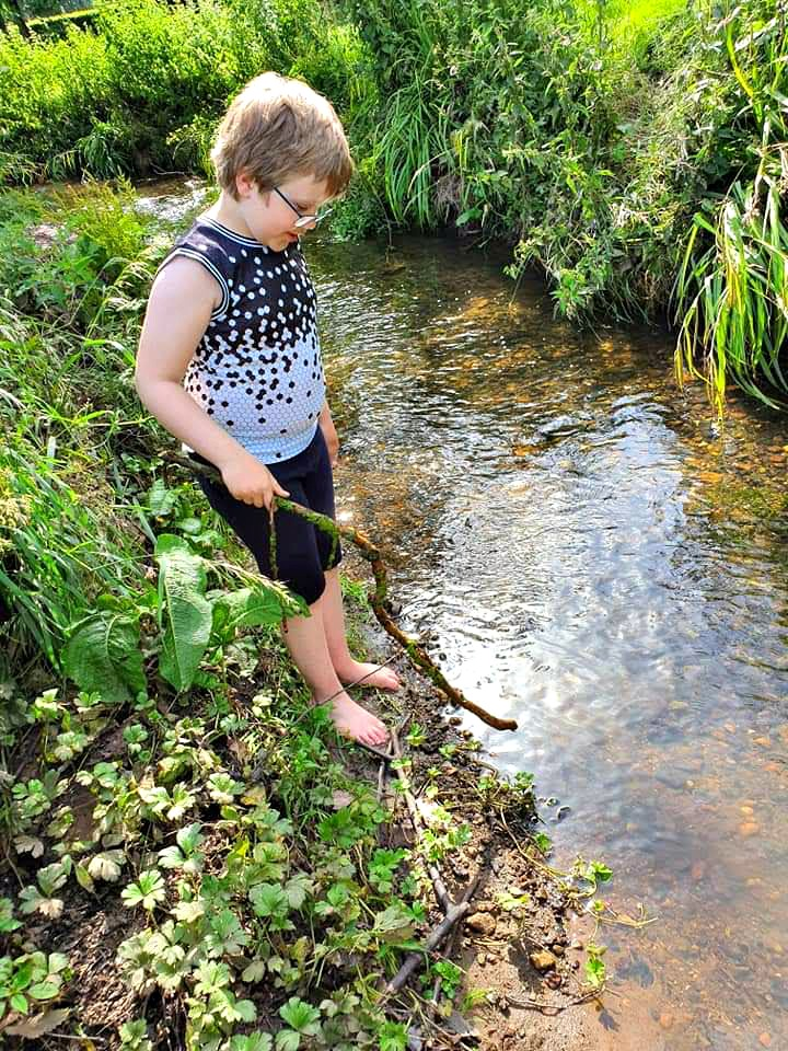 boy with stick standing at the edge of a stream