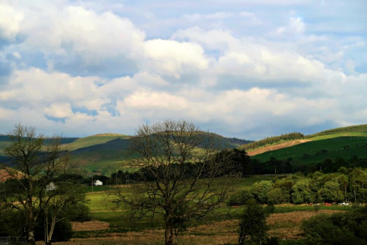Photograph of a green field with hills in the background and a cloudy sky scape. Lots of trees are also seen. taken at Thynrhyd retreat in Wales, UK