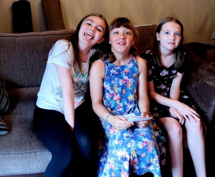 Three girls sitting on settee