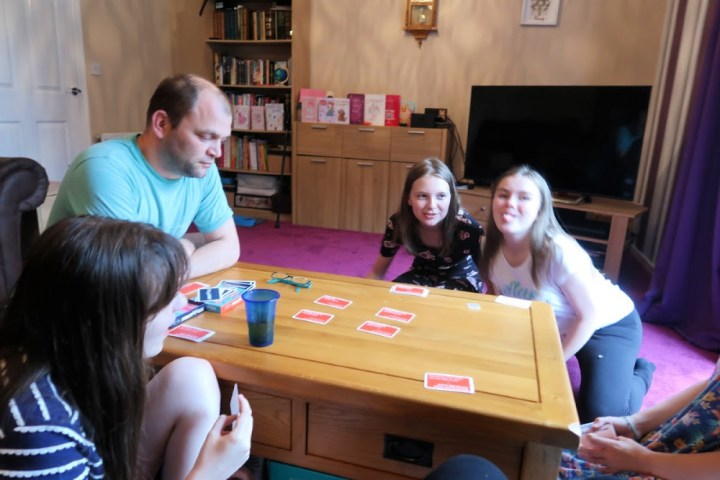 kids and adult sitting around the table playing a card game