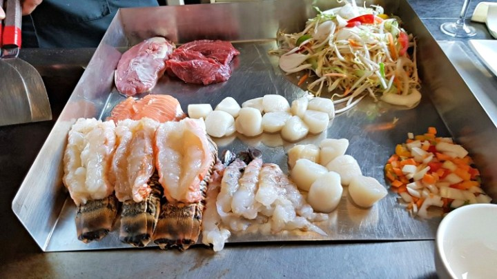 tray of uncooked meat, fish noodles and vegetables.