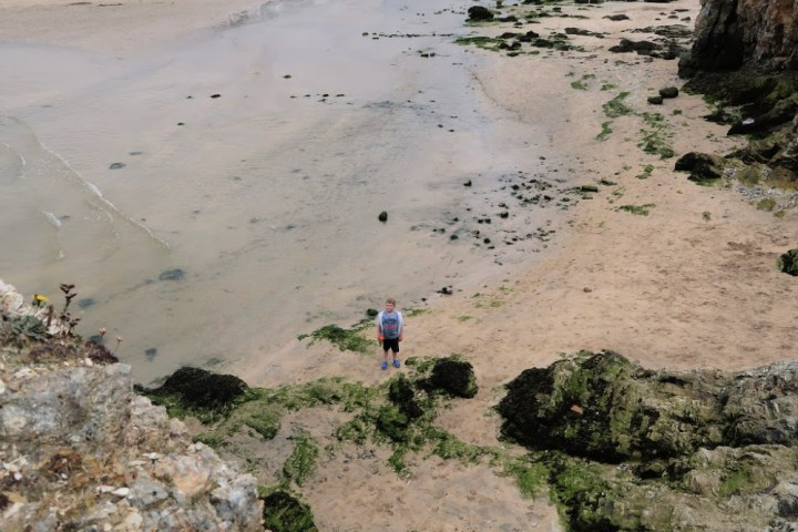 Image taken from a cliff side looking down on the beach where a little boy is standing looking up.
