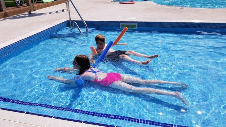 A girl and a boy floating in a small outdoor pool