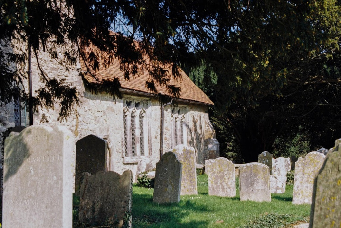 a photograph of an old church with stones in the cemetery