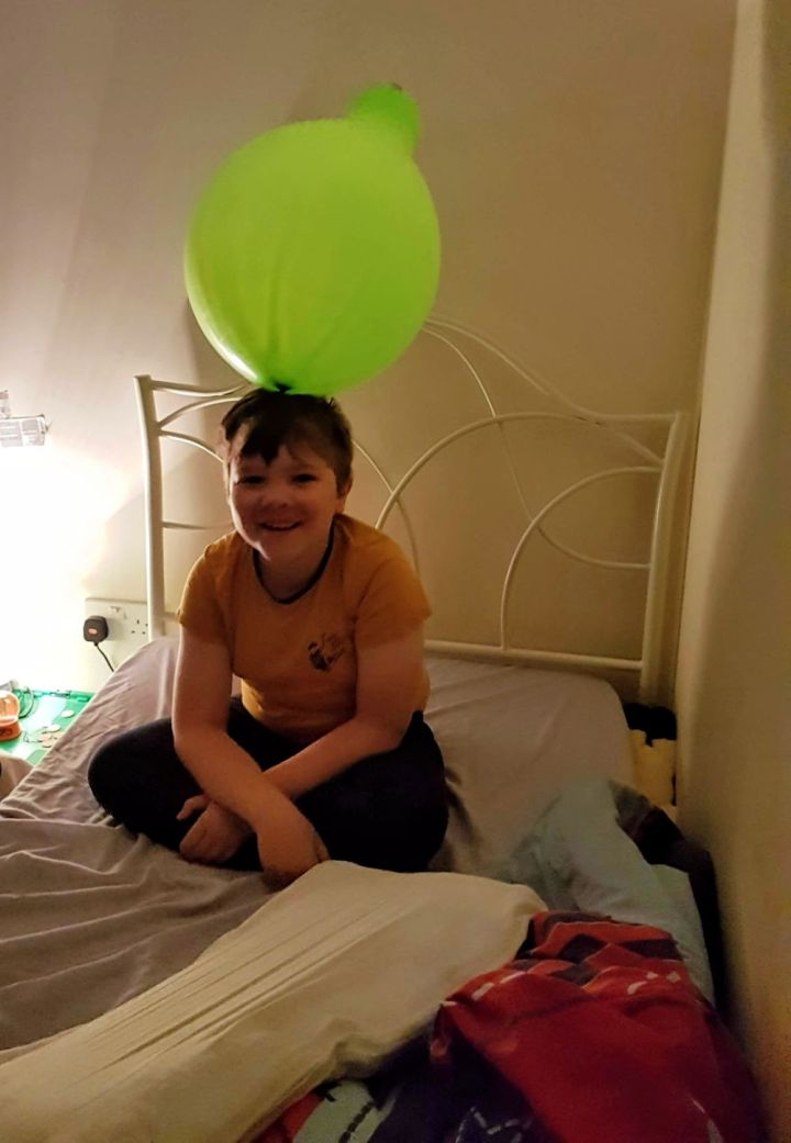 silly boy, with a big green balloon on his head.