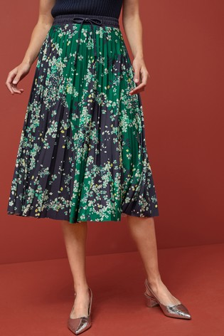 A pleated grean floral patterened skirt on a model shown from the waist down with silver shoes