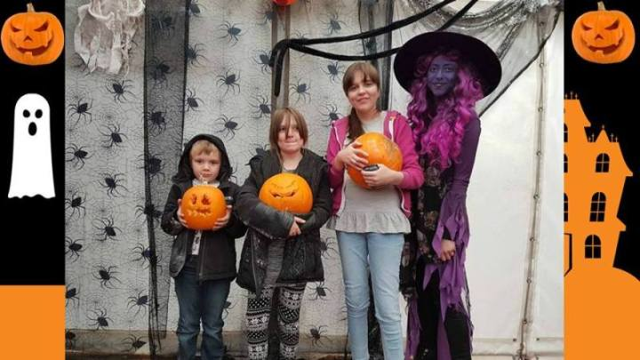 three children and a purple witch holding pumpkins inf ront of a spooky background.