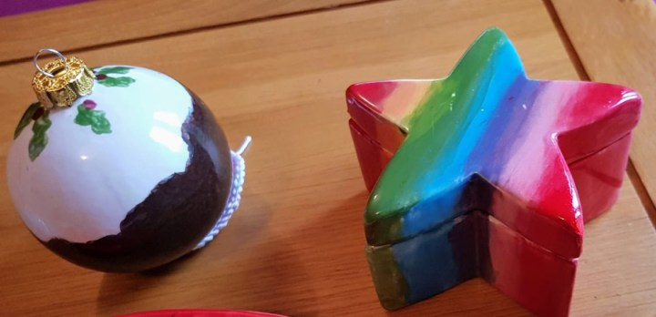 two painted pieces of pottery, ones is a Christmas pudding and the other a rainbow star box