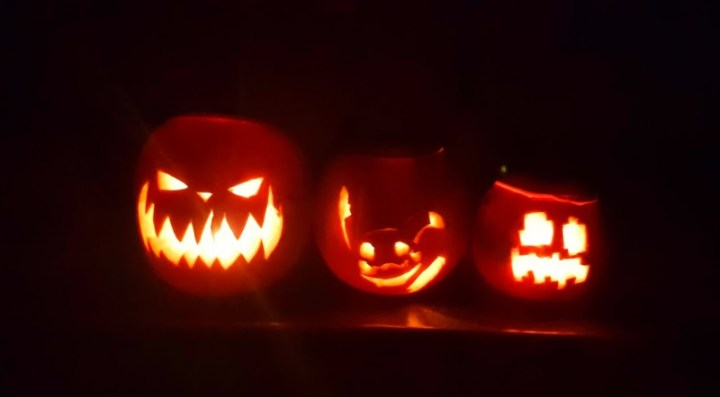 three scary pumpkins in a row, lit up in the dark