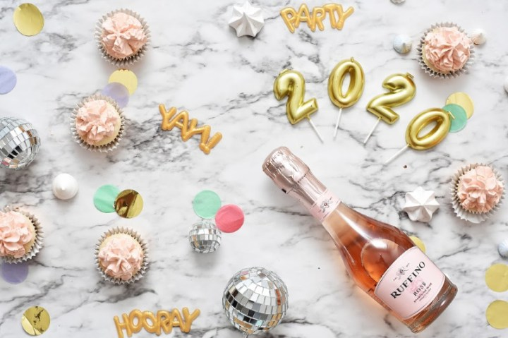 2020 celebration with a bottle of champagne and cupcakes