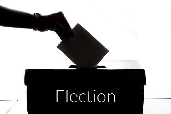 hand posting a card in a ballot box with the word election.