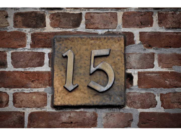image shows the number 15 on a plate on a brick wall. fifteen