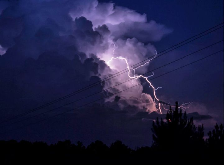 photo shows dark sky with a flash of lightning coming from the clouds.