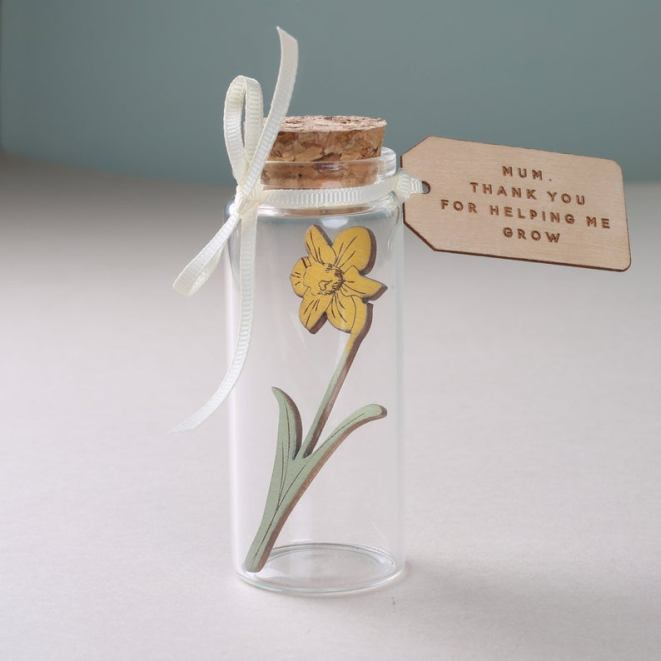 daffodil in a bottle with a little message etched on wood.