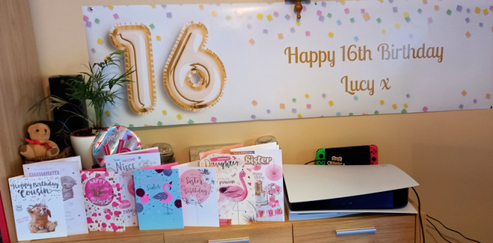 A special birthday banner with a big 16 on it and Happy Birthday, underneath is a row of birthday cards and an obtrusive PS5 games console