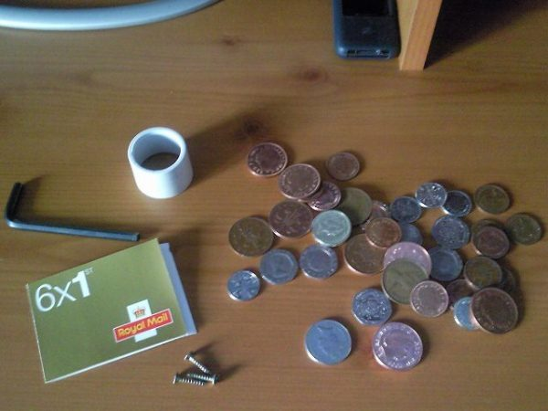 Contents of a pot of change include things other than money: stamps, Allen wrench, roll of tape, screws.