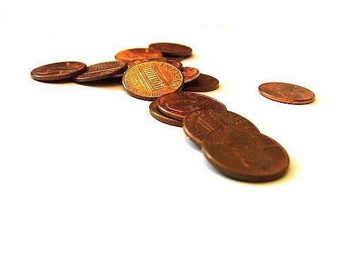 A couple of a dozen pennies on a white surface.