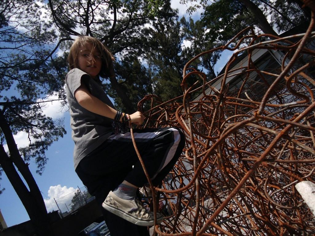 Miro exploring an interactive outdoor sculpture of rusty rebar.