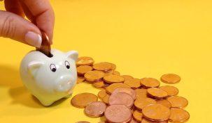 mano poniendo moneda de 5 centimos de euro en mini hucha cita con tu independencia económica