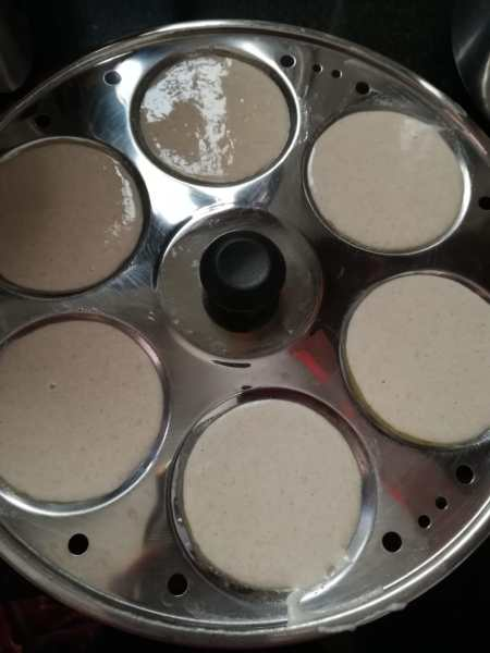 Idli batter in greased idli moulds