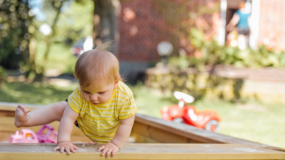 Baby climbing out of a sandbox