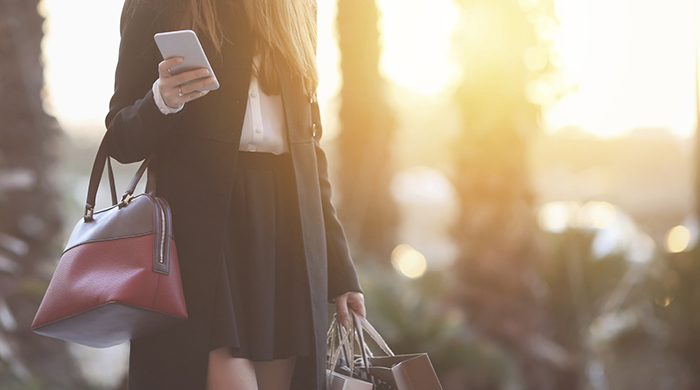 Woman in hat holding iPhone and shopping bags