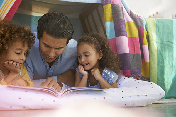 Shot of a young father lying in a tent fort with his children and reading them a book