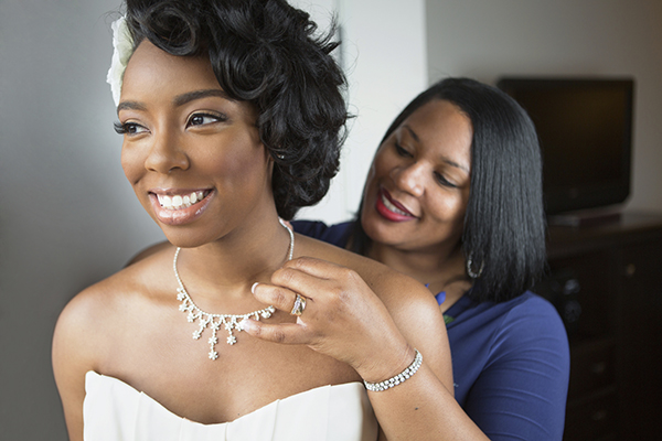 Mother of the bride putting necklace on daughter