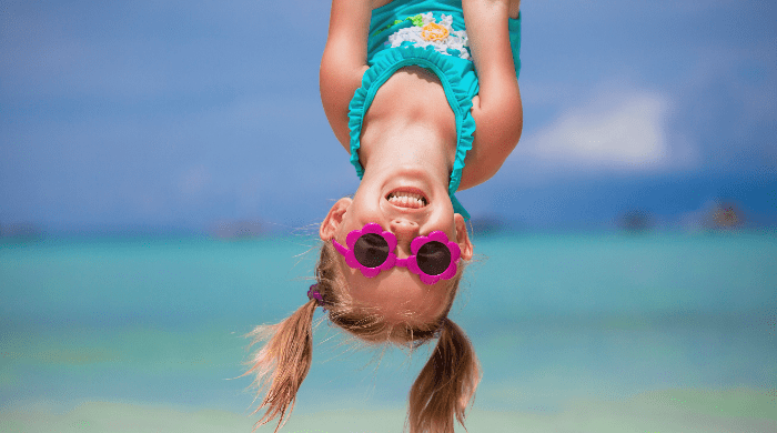 Little girl in bathing suit hanging upside down