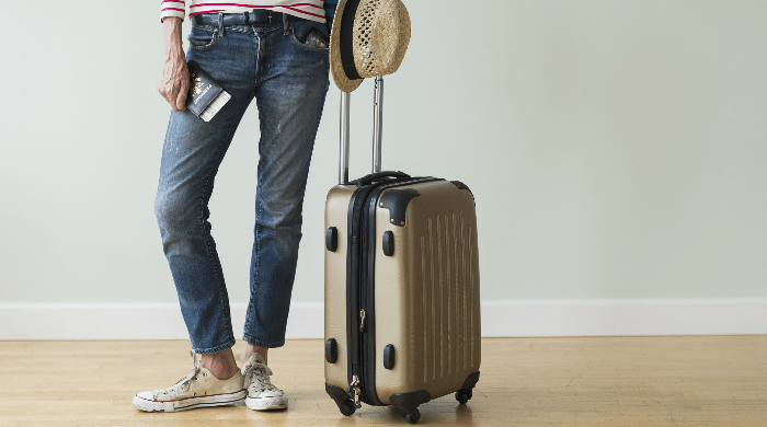 Woman with rolling suitcase and passport