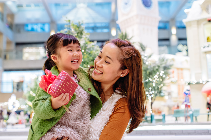 Pretty young mom carrying lovely little daughter who's holding a beautifully wrapped present in her hand, they both smiling joyfully while talking to each other in front of the lighting decoration in the shopping mall
