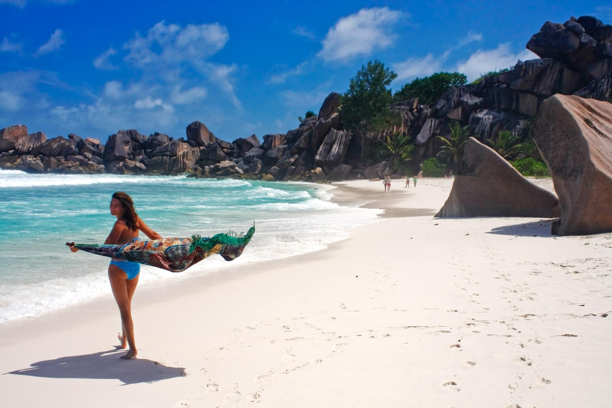 Young woman walking on tropical beach called Grande Anse, La Digue Island, Seychelles, Indian Ocean.