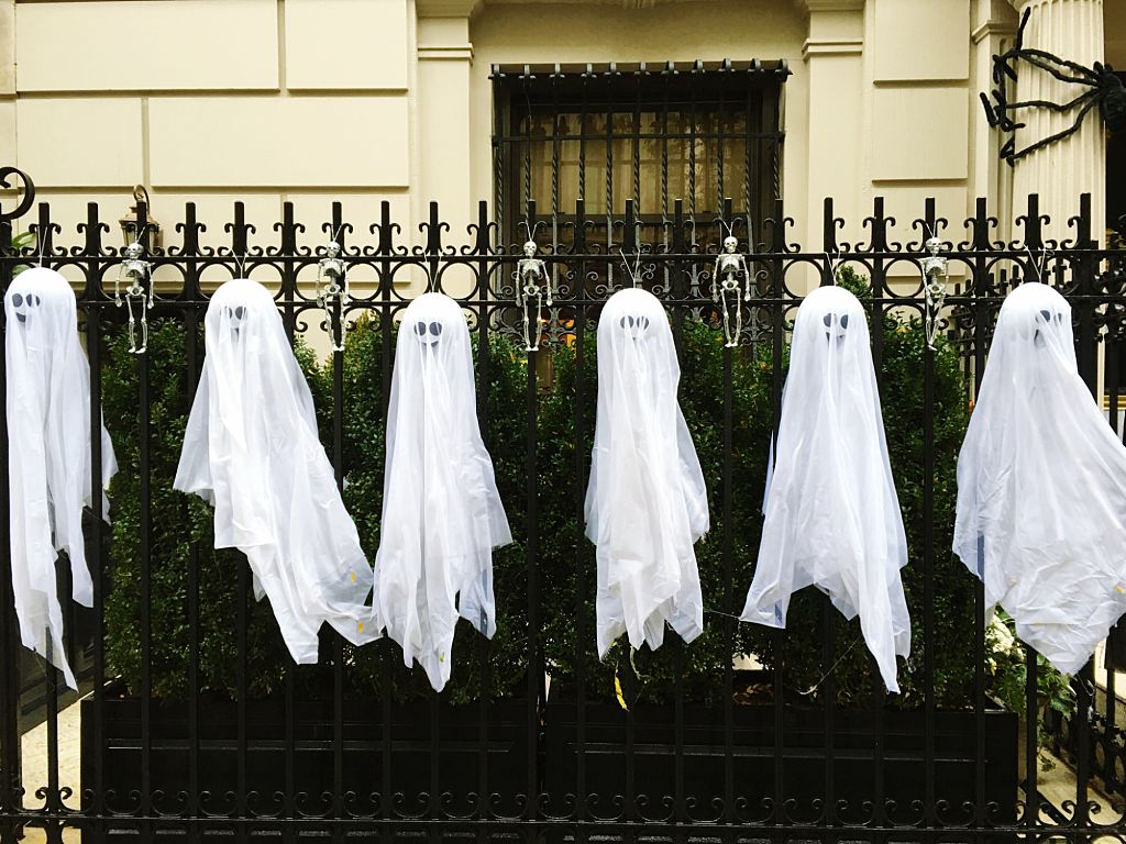 Artificial Ghosts Hanging On Fence Outside House