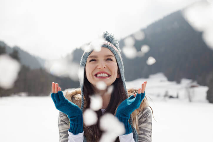 Woman wearing a beanie and gloves in the snow