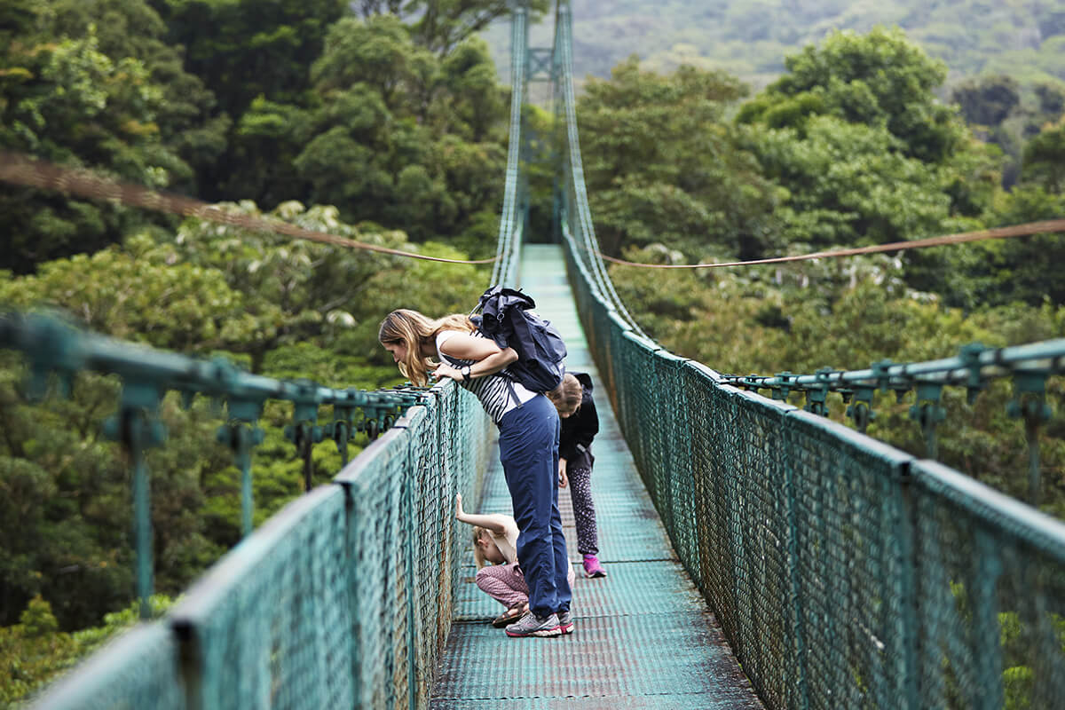 Mom and kids looking over a bridge
